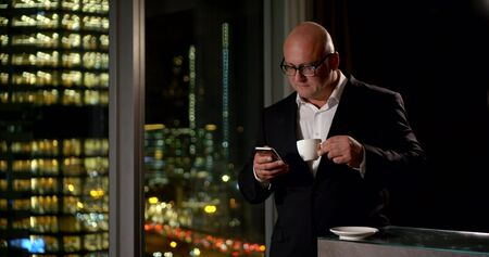 A business man in glasses stands in a room at the panoramic window, behind which you can see the lights of the night city, he looks at the phone, he stands at the counter and drinks a Cup of coffee. Archivio Fotografico