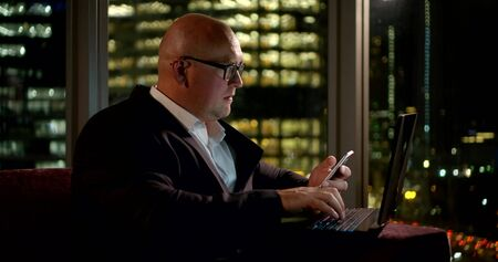 a business man, wearing a classic suit, he sits in the office on the couch at the window, behind which you can see the lights of the city, he holds a phone in his hand and in front of him is a laptop.