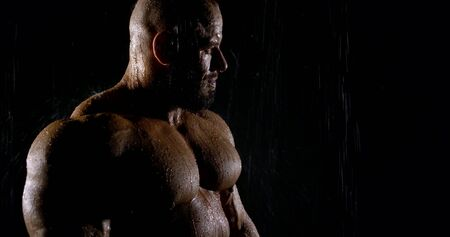 close up male brutal portrait of a professional athlete in a dark room under the shower