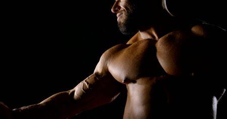 Brutal bearded professional athlete with dark room posing showing bicep shoulder. Anabolic steroids Reklamní fotografie