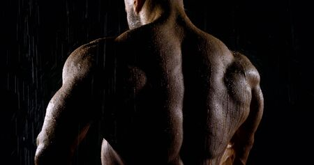 close up male muscular huge back of a professional athlete in a dark room under the shower