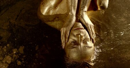 excited woman covered golden dye is stroking herself, lying in water, stroking skin of face and neck