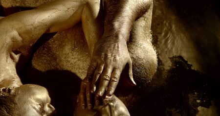 man and woman covered by gold are embracing in water