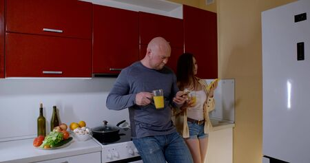 married couple is using cell phones on kitchen in flat, drinking juice in morning, family breakfast