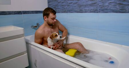 crazy man is sitting in bath and playing with his dog, singing and dancing Stock Photo
