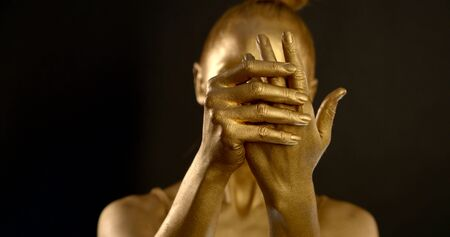 woman looks like golden sculpture is stroking and demonstrating her palms