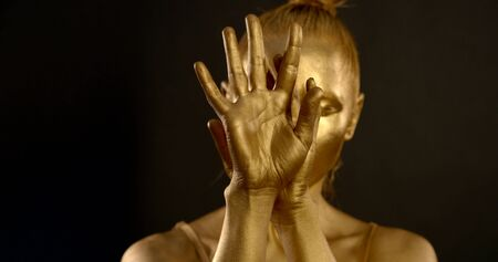 close-up of female hands with Golden glowing skin. they turn, palms open and close. in the background, a girl is seen out of focus. black background