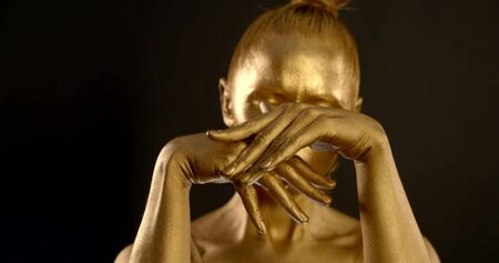 close-up of female hands with Golden glowing skin. they turn, palms open and close, fingers Flex and unbend and stroke each other. in the background, a girl is seen out of focus. black background 写真素材