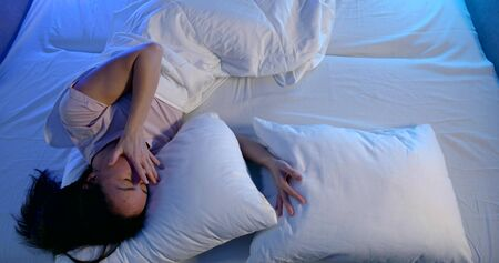 Close-up of a dark-haired woman lying in a light white bed with two pillows, she wakes up, yawns, stretches and picks up the phone.