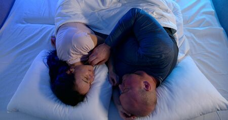 an adult couple is lying on white bed linen. a bald man touches his wifes face and strokes her back. a woman with long hair smiles. the view from the top. blue bottom light