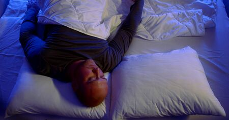 lonely middle aged man is lying in double bed at nighttime, boring and do not sleep, loneliness and longing