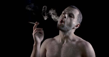 portrait of an unshaven brunette with very pale skin on a black background. a man smokes a cigarette, rounds his mouth, lets out smoke rings, takes a drag