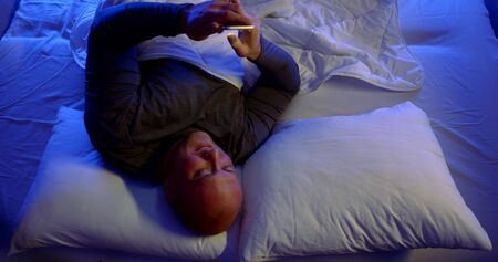 cheerful single man is lying in bed at night, browsing internet by smartphone, viewing social nets