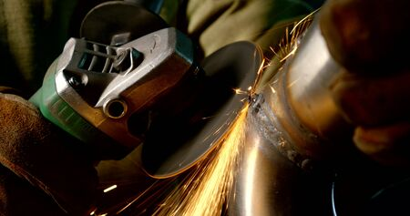 close-up of a hand sander. it grinds not a neat rough weld on a metal pipe. strong stream of sparks