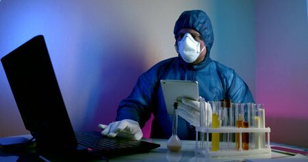 a middle-aged virologist is in the lab, sitting at a table with a laptop, and on the table are flasks with urine tests. He is wearing a blue work suit, has a hard hat on his face and gloves on his hands, and is holding a tablet.
