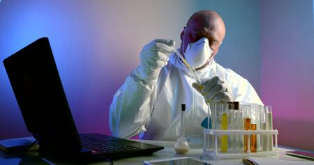 portrait of a man, a virologist, is in the laboratory, he sits at a table on which there is a laptop and there are flasks with tests, he examines infections, coronovirus. He is wearing a white work suit, a mask on his face and gloves on his hands.
