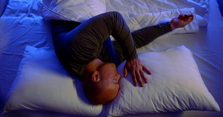 a bald man in dark pajamas is lying on white bed linen. he strokes the empty pillow next to him, covers his eyes with hand, and cries. the view from the top. blue bottom light
