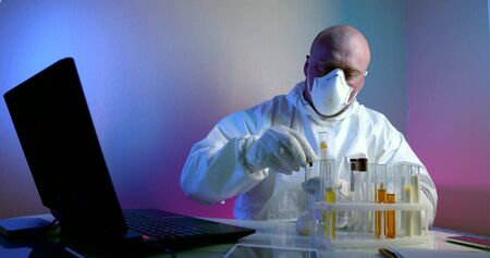 a bald, middle-aged virologist is in the lab, sitting at a table with a laptop, flasks of tests on the table, examining the tests. He is wearing a white work suit, a mask on his face, and gloves on his hands.