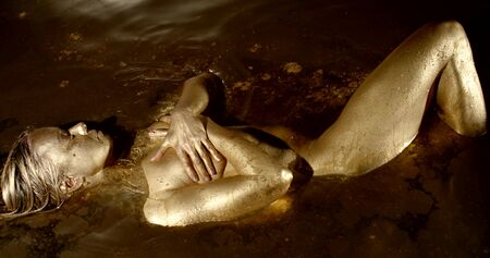 The body of a adult woman lies in the water covered with gold paint
