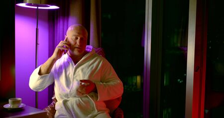 Bald adult man in white robe sits in a chair in the evening at home and speaks on the phone