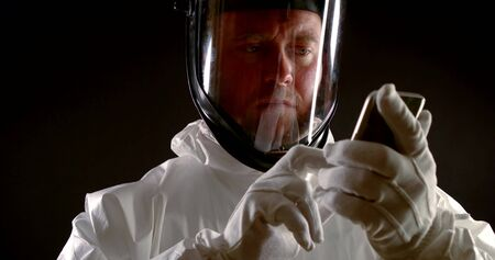 a man is dressed in white protective clothing, a mask with a transparent visor and gloves. he holds the phone in his hands and points at the screen. black background