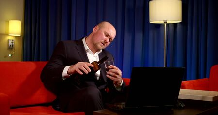 a bald man in a dark suit is sitting on a red sofa in front of a laptop against a blue curtain. he holds a bottle in his hand, pours wine into a glass, refills it, and SIPS it
