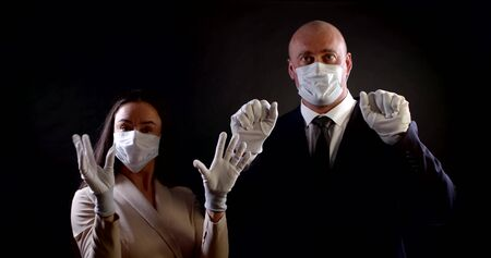 funny man and woman with face masks are showing palms dressed protective gloves
