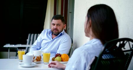 A close-up portrait of a dark-haired woman and a bearded man sitting opposite each other at a table in a cafe on the street, chatting, on the table they have fruit, pastries, glasses of juice and cups
