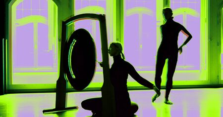 female black silhouettes against arched Windows. a woman sits in front of the Gong and strikes it. the other is dancing. the image is split. the colors change