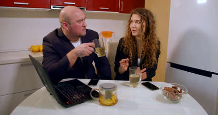 A bald man in a jacket and a curly-haired girl in a jacket and a white top sit at the kitchen table and drink tea from transparent cups, laugh, communicate