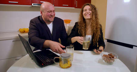 A bald man in a jacket and a curly-haired girl in a jacket and are sitting at the kitchen table and drinking tea from transparent cups, laughing, in front of them on the table is sweets and a laptop.