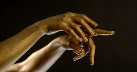 beautiful hands covered with gold move in dancing style