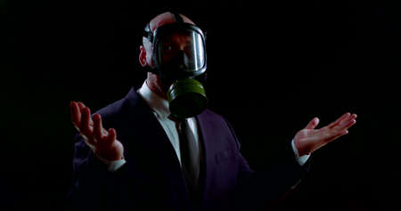 a man in a business suit stands in the dark with a gas mask on his head during environmental contamination Banco de Imagens