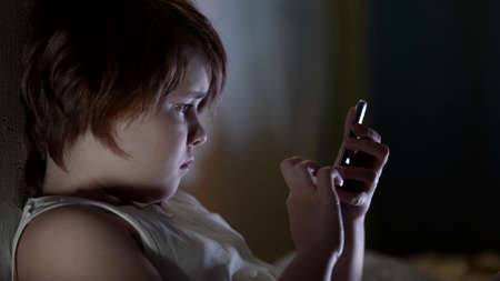 little girl is chatting online in internet by smartphone, lying in bed at night time