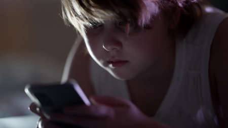 little girl is using smartphone with internet at nighttime, before sleeping, internet addiction