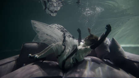 A female model in a long dress and heels poses beautifully on a gray sofa with pillows, which is under water. It floats up. bubbles float around. Her skirt and hair flutter under the water.
