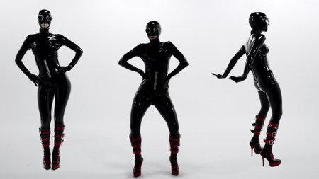 three women dressed black latex costume are dancing at white background