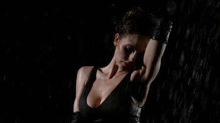 alluring brunette woman is standing under water flows in darkness, female body is getting wet Banque d'images