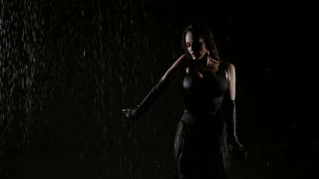 enigmatic female figure in darkness under rain, woman is moving slowly, seduction and temptation