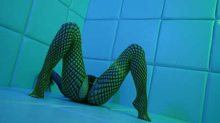 eccentric lady is wearing net bodysuit is lying on floor and posing voluptuous