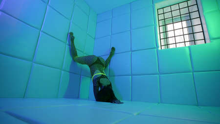 depraved woman is posing strange and sexually in room, lifting legs on wall, standing on hands