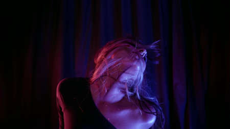voluptuous woman is dancing exotic dance in darkness at home, strange artistic makeup
