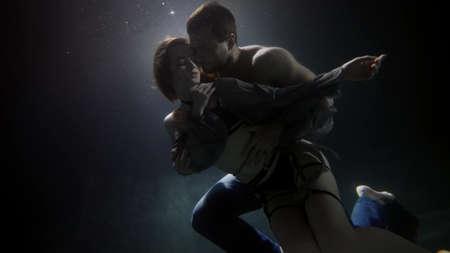 young loving pair is hugging underwater, man is stroking his beautiful girlfriend dressed lingerie