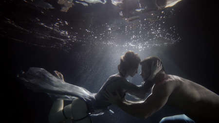lovers underwater, beautiful woman and handsome man are floating in darkness