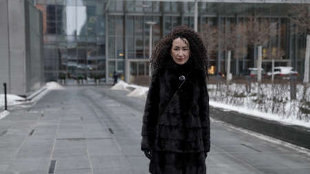 rich brunette woman dressed fur coat is walking in big city at winter, strolling in business district at daytime