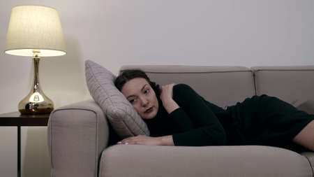 tired young woman is lying on couch at evening and relaxing, trying to sleep Foto de archivo