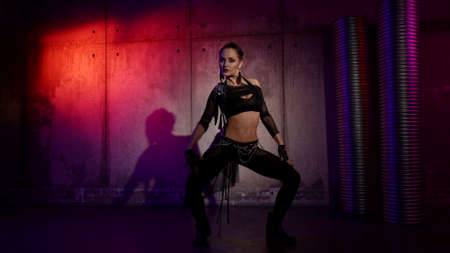 sexy female dancer is dancing in studio, performing modern choreography