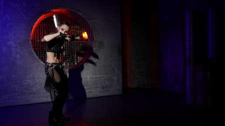 sexy female dancer is dancing alone in dark studio with modern decoration