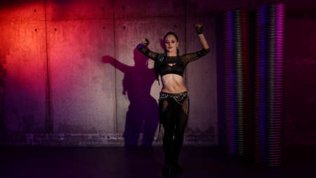 sexy woman is dancing modern choreography, using movements from belly dance, vogue and electro dance