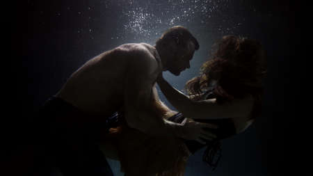 breakup of loving couple underwater, floating in depth, man and woman are embracing